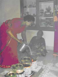 My aunt putting some milk in the Pongal pots, over a highly polluting indoor wood stove